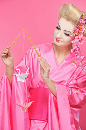 Beautiful geisha with an origami birds photo