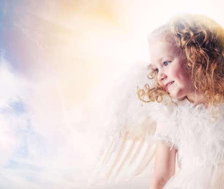 Niña de Ángel contra el cielo soleado