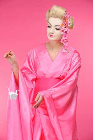 Beautiful geisha holding origami bird Stock Photo - 6819176