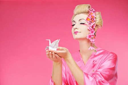 Beautiful geisha holding origami bird  photo