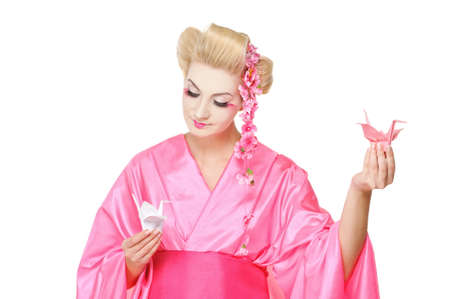 Beautiful geisha holding origami birds photo