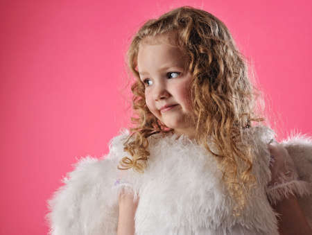 Beautiful little angel girl isolated on pink background photo