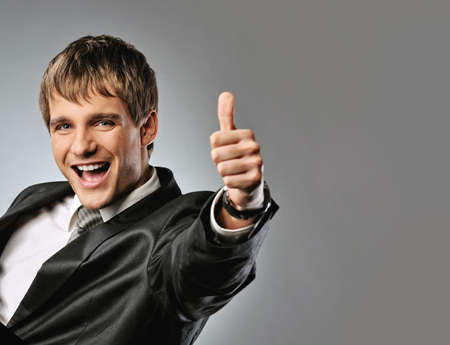 Happy businessman showing his thumb up with smile   photo