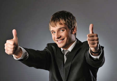 Happy businessman showing his thumbs up with smile   photo