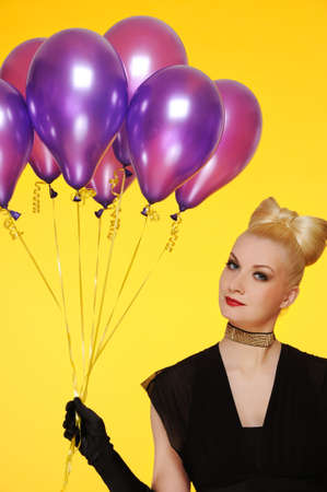 Beautiful lady with a bunch of purple balloons photo