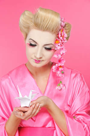 Beautiful geisha holding origami bird Stock Photo - 6976493