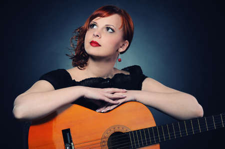 Attractive redhead woman with guitar photo