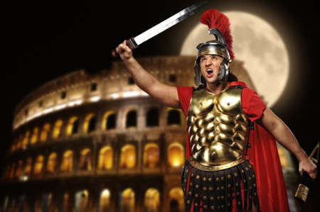 gladius: Roman legionary soldier in front of coliseum at night time
