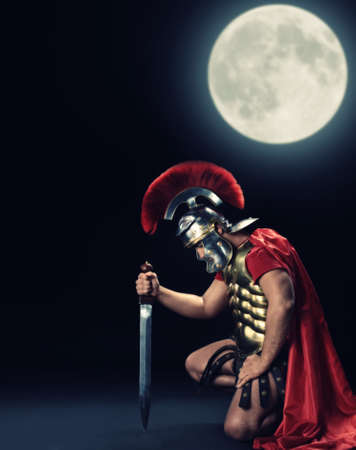 Legionary soldier standing on a knee at night time Stock Photo - 6976501