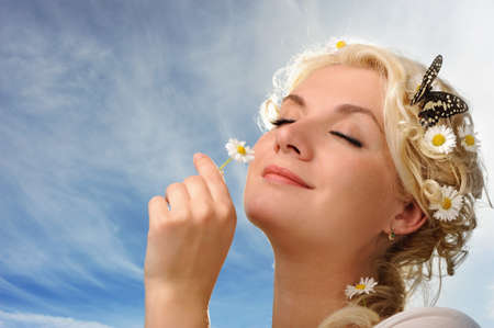 Lovely woman with a butterfly over blue sky photo