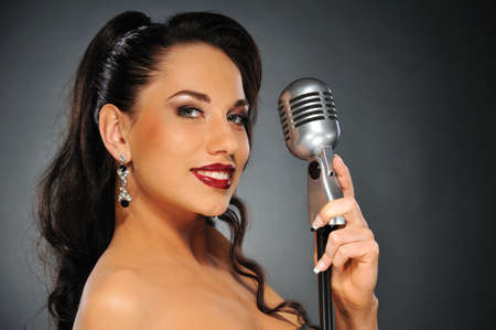 Portrait of a beautiful brunette with a retro microphone photo