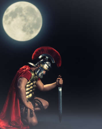 roman soldier: Legionary soldier standing on a knee at night time Stock Photo