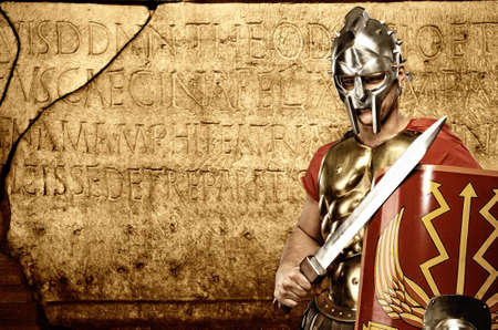 roman soldier: Roman legionary soldier in front of abstract wall Stock Photo