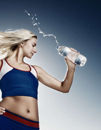 outdoor sports: Young woman drinking water after fitness exercise