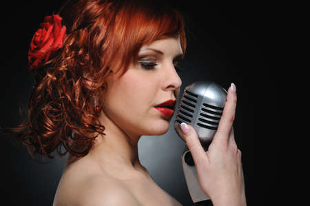 Attractive redhead woman with retro microphone photo