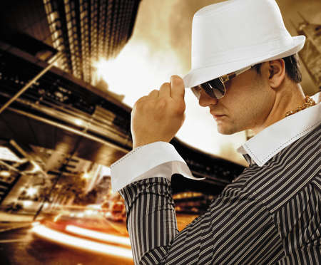 night shirt: Stylish man in a hat in front of night city