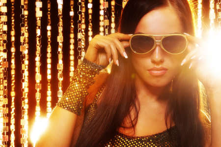 Attractive woman in sunglasses over golden curtains photo