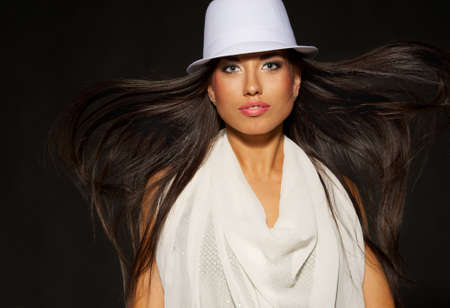 Attractive lady in white hat and blowing hair photo