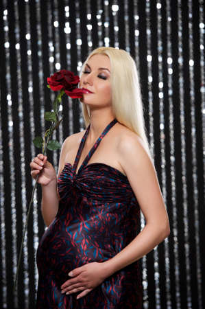 Attractive pregnant woman with red rose photo