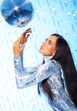 Brunette woman with a disco ball over abstract background photo