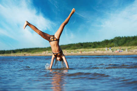 young girl making cartwheel in the water Stock Photo - 8131722