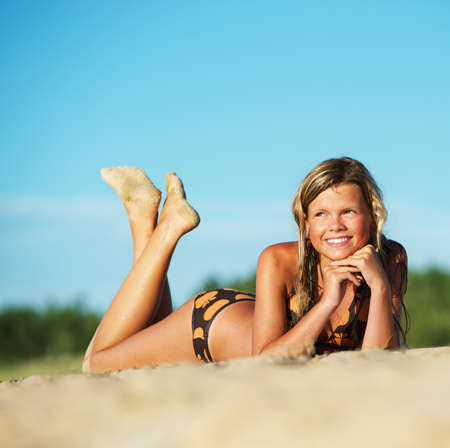 Beautiful young girl relaxing on the beach photo