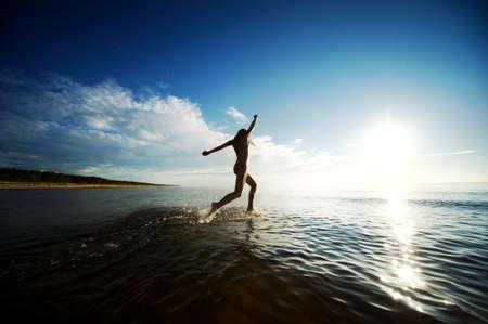 Happy girl running in the sea Stock Photo - 8131725