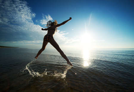 Girl jumping in the sea photo
