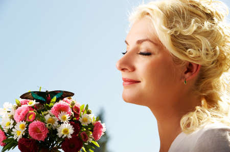 Beautiful blond woman with fresh flowers and butterfly photo