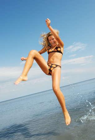 Happy little girl having fun on a beach photo
