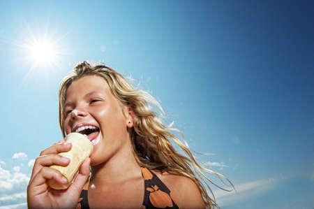 Happy girl eating icecream outdoors photo