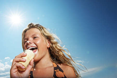 smiling sun: Happy girl eating icecream outdoors Stock Photo