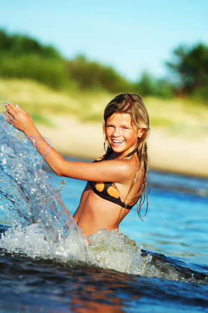 Young happy girl making water splashes photo