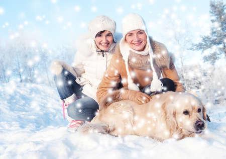 labrador christmas: Friends playing with golden retriever outdoors