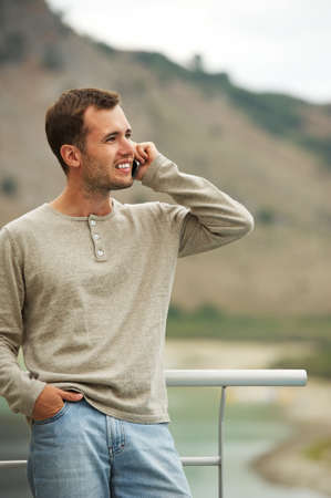 Handsome man with mobile phone outdoors photo