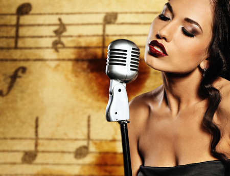 Beautiful singer against abstract background photo