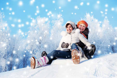 Mother and daughter sliding in the snow photo
