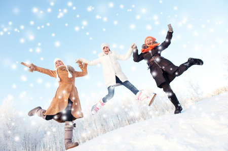 Happy girls jumping in the snow photo