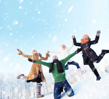 Happy friends jumping in the snow photo