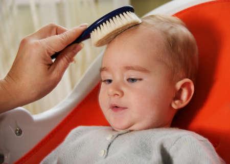 Mother combing her babys hair photo