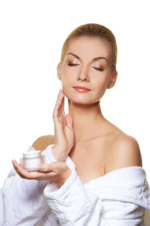 ner: Woman applying moisturizer cream on ner face Stock Photo