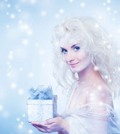 Beautiful snow queen with a christmas box    photo