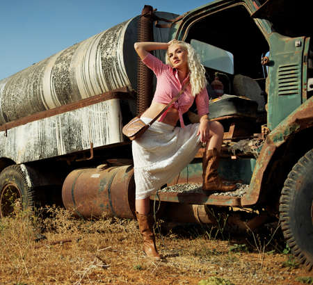 Attractive blond woman near the old car photo