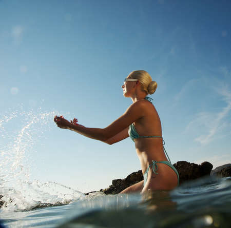 underwater woman: Attractive woman making water splashes in the sea