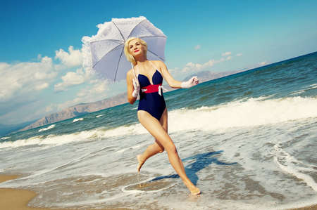 Attractive blond woman running in the sea photo