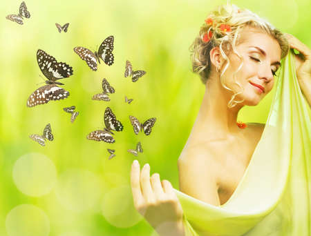 Beautiful young woman and flying butterfly photo