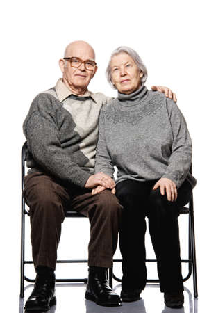 sitting chair: Portrait of a happy senior couple embracing each other Stock Photo
