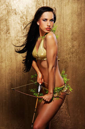 Attractive sexy woman shooting an arrow photo