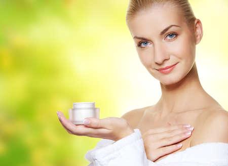 Woman applying moisturizer cream on her body photo