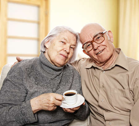 Happy senior couple drinking coffee at home photo